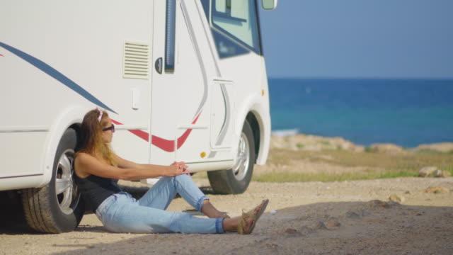 Meisje toerist in de buurt van haar trailer op parkeren in de buurt van zee video