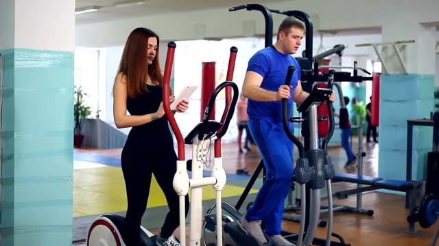 Girl trainer sports man ellipsoid on simulator  involved video