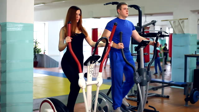 Girl trainer sports man on simulator ellipsoid involved video