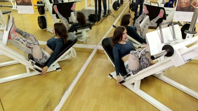 vídeos de stock e filmes b-roll de a girl trains the muscles of her legs in gym, she makes the leg press lying down - peso equipamento para exercícios