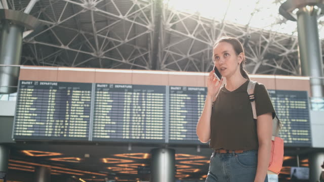 Girl traveler at the airport to talk on a mobile phone