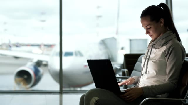 girl traveler freelancer in sportwear uses laptop for work in airport lounge - usare il laptop video stock e b–roll