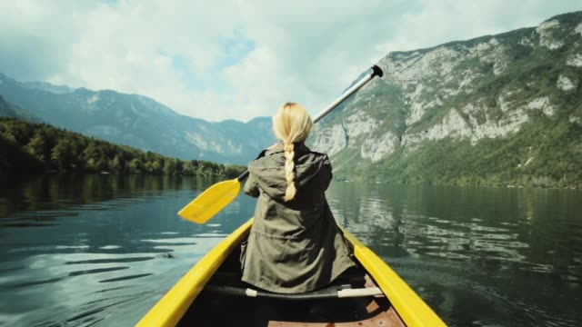 Girl traveler swims in boat on mountain lake. Girl traveler swims in boat on mountain lake surrounded by high mountains. Girl in canoe rowing leisurely paddle along calm lake. Woman in the boat from the back. denmark stock videos & royalty-free footage