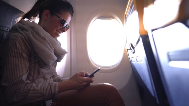 girl traveling by plane and using mobile phone - comodità video stock e b–roll
