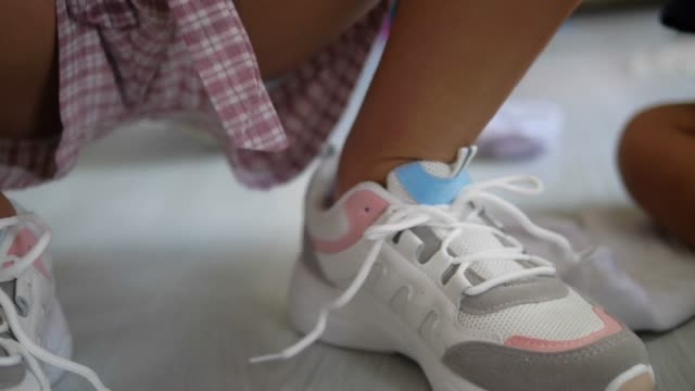 Girl tries to tie white shoes, slow motion.
