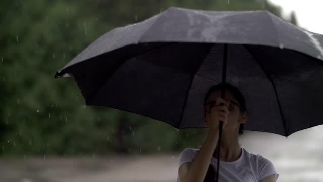 vídeos de stock, filmes e b-roll de rapariga gira um guarda-chuva com tempo chuvoso e relógios como pingos de chuva bateu em um guarda-chuva, humor outono, câmera lenta - setembro amarelo