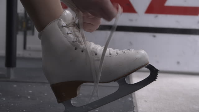 dziewczyna wiązanie sznurowadła z łyżwy - łyżwa filmów i materiałów b-roll