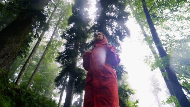 Girl under summer rain in forest
