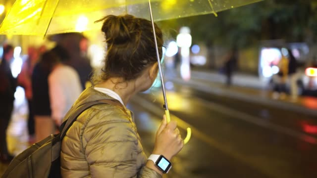Girl under umbrella waiting on bus stop at night