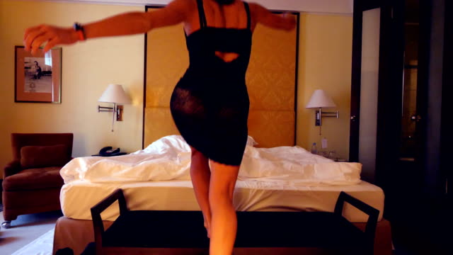 Girl undresses for her partner in front of a bed in an hotel room video