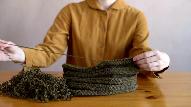 Girl unravelling the knitted hat video