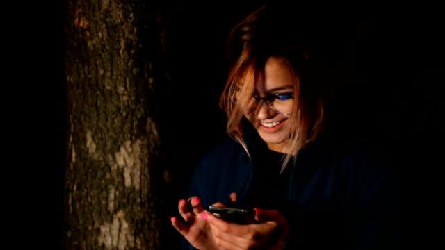 Girl uses smartphone at night near tree video