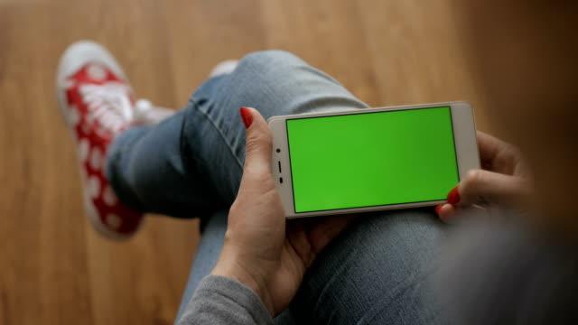 ragazza che usa il cellulare.  donna che tiene uno smartphone nelle mani di uno schermo verde schermo verde, mano dell'uomo che tiene lo smartphone mobile con chiave cromatica schermo verde su sfondo bianco. concetto tecnologico. - composizione orizzontale video stock e b–roll