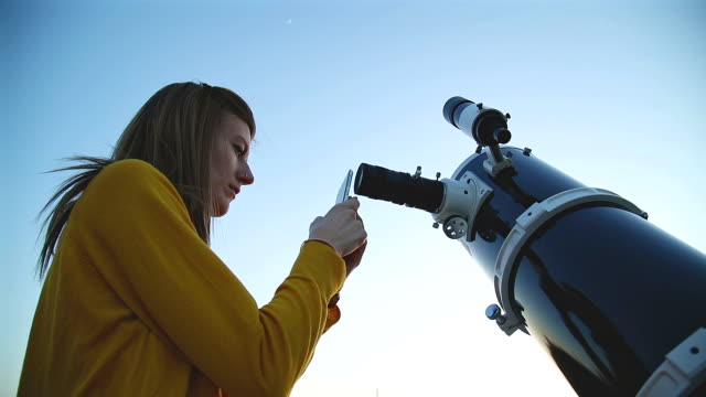 Girl using cellphone and photographing through a telescope. video