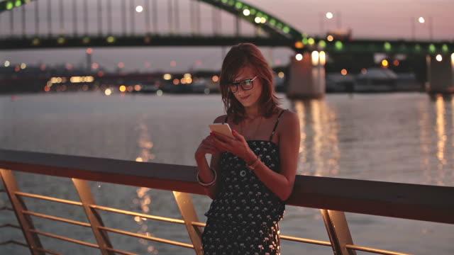 Girl using cellphone in city / urban surroundings - near river. video