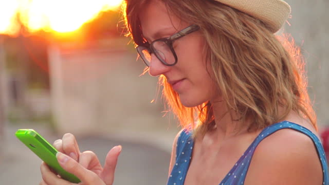 Girl using cellphone on the street on a sunny summer day. video