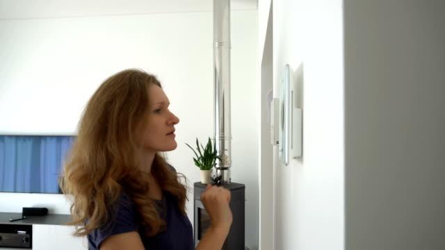 flicka som använder styrenheter för att styra värme-, ventilations- och smarta hemfunktioner - kvinna ventilationssystem bildbanksvideor och videomaterial från bakom kulisserna