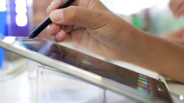 Girl using digital Pen drawing on tablet video