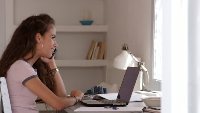 Girl using laptop in bedroom takes a call on her phone, shot on R3D video