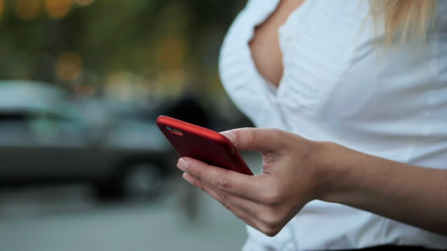 Girl using mobile phone - Smartphone in th city. Young beautiful blonde businesswoman surfing on her cellphone. Woman wearing white shirt. Slow motion video
