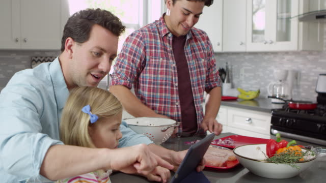 Girl using tablet in kitchen with male parents, close up, shot on R3D video