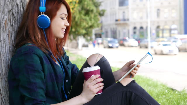 Girl using tablet pc and enjoying the music video
