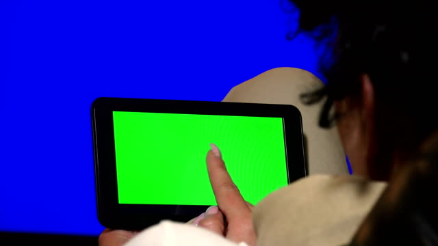 Girl Using Tablet PC with Green Screen. UHD stock video, alpha matte included video