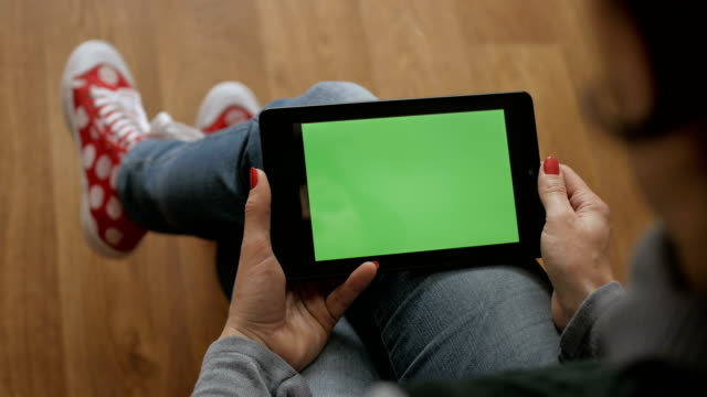 Girl Using Touchscreen Mobile Tablet. Young Woman Home Sitting on a Chair with Green Screen Tablet in Horizontal Mode. Girl Using Smartphone, Browsing Internet, Watching Video Content, Blogs. POV.