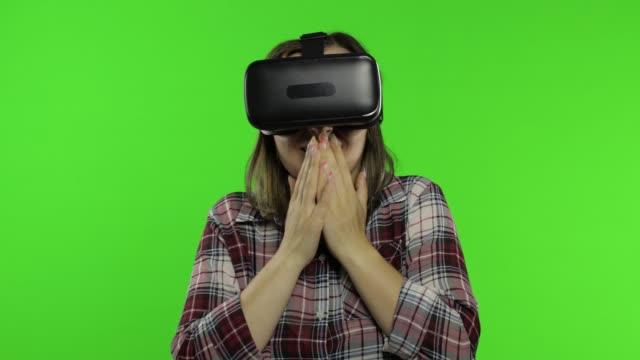 flicka som använder vr app hjälm för att spela simulering skrämmande spel. kvinna tittar virtuell verklighet 3d-video - endast unga kvinnor bildbanksvideor och videomaterial från bakom kulisserna