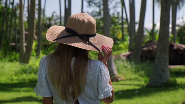 vídeos y material grabado en eventos de stock de niña vacacionista dando un paseo por el bosque de palmeras tropicales y disfrutando del calor del verano - disquete