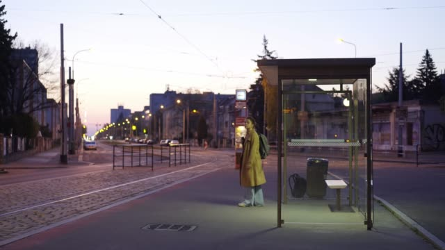Girl waiting on bus stop shelter at night Illuminated bus stop in residential area on the outskirts of the city at night. View through modern transparent shelter lonely young girl waiting public transport, coming to approaching tram bus stop stock videos & royalty-free footage