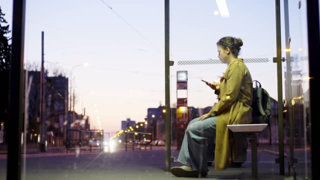 Girl waiting on bus stop shelter at night Illuminated bus stop in residential area on the outskirts of the city at night. View through glass of transparent shelter on roadside, sitting young girl using smartphone while waiting bus bus stop stock videos & royalty-free footage