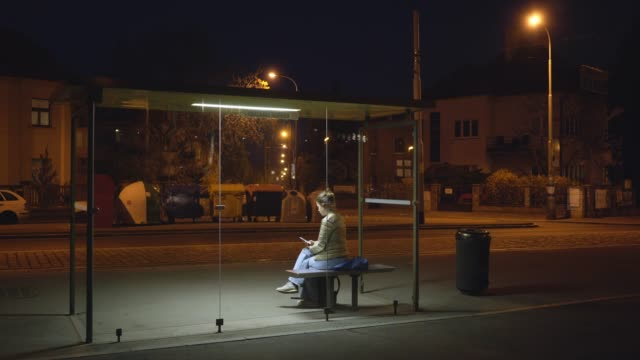 Girl waiting on bus stop shelter at night Illuminated bus stop in residential area on the outskirts of the city at night. View through modern transparent shelter alone young girl sitting on bench and chatting via smartphone while waiting bus bus stop stock videos & royalty-free footage