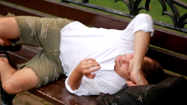 girl wakes up the sleeping man on the bench. man wakes up from sleep video