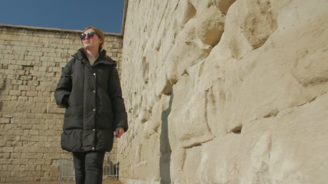 Girl Walk And Rock Architecture Girl walk and rock architecture old roman ancient yellow temple egyptian sand wall with windows low low angle track camera movement hungary stock videos & royalty-free footage