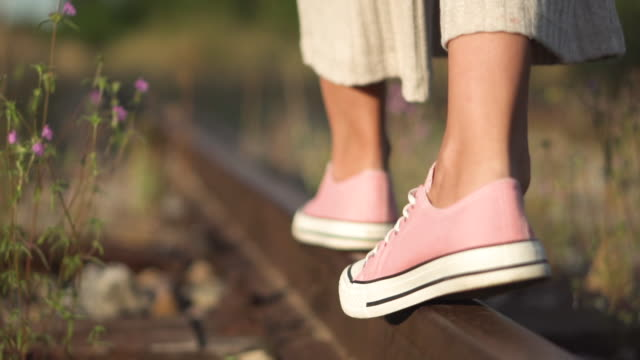 Girl walking along railroad rail. Romantic slow motion tracking shot of young girl feet close-up walking along railroad rail at summer.