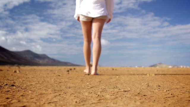 Girl walking away from camera on dry land video
