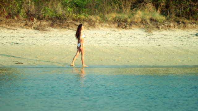 Girl walking barefoot on the water along deserted beach. Woman walking on a tropical beach. Young girl on an empty tropical beach on the deserted empty island. Ocean view, slow motion Shot on Red Weapon Digital Cinema Camera. 100fps turks and caicos islands stock videos & royalty-free footage