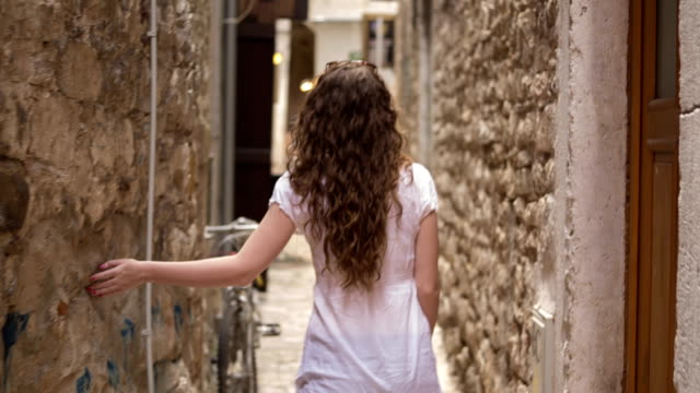 Girl walking between two old walls video