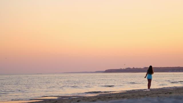ragazza che cammina in onde d'acqua di mare sulla spiaggia al bellissimo tramonto - dorso umano video stock e b–roll