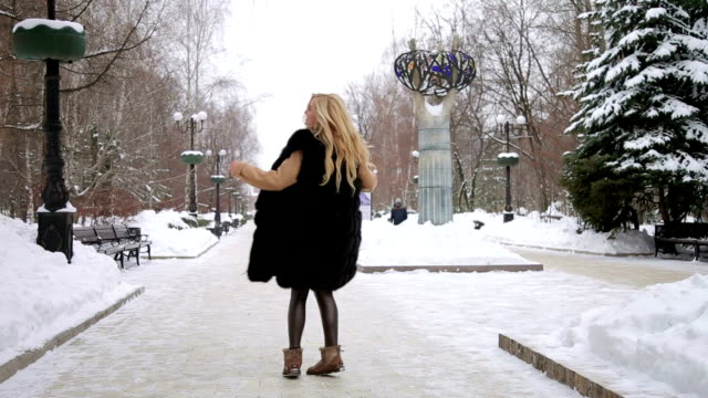 Girl walking in the snow-covered Park. video