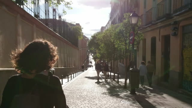 girl walking in the streets of malasaña madrid at sunset - madrid video stock e b–roll