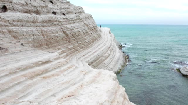 女孩走在岩石上,大海在背景 - sicily 個影片檔及 b 捲影像