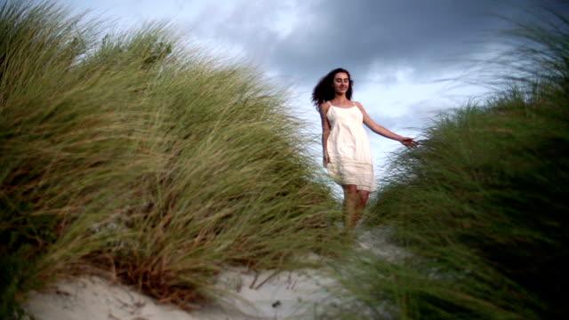 Girl walking through beach dunes at sunset video