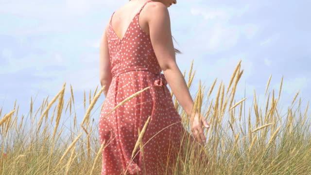 girl walking through sand dunes and grass - krajobraz morski filmów i materiałów b-roll