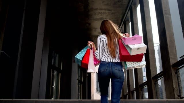 vídeos de stock, filmes e b-roll de garota subindo as escadas do shopping central com sacolas de compras e começar a dançar. black friday - arméria
