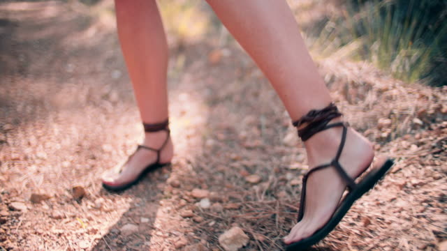 Girl walking with sandals in forest