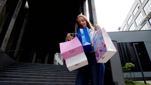 vídeos de stock, filmes e b-roll de menina andando com sacolas de compras, olhando satisfeito com a compra, desfrutando de descontos na black friday - arméria