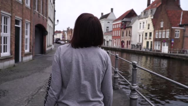 girl walks and looks at attractions in the city of bruges belgium. slow motion - bruges video stock e b–roll