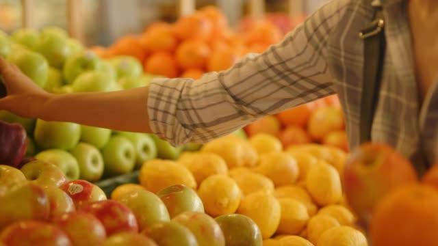 la ragazza va in giro per il negozio di alimentari e sceglie frutta e oggetti adeguati - mercato frutta donna video stock e b–roll